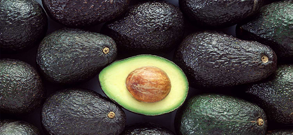 Pile of avocados, with one sliced open