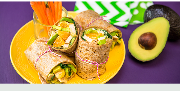Fresh vegetable, fruit, and avocado wrap with a side of carrots.